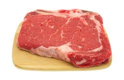 Bone in rib eye steak on wood cutting board Royalty Free Stock Photos