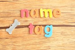A bone shape name tag for a dog with the word name tag Royalty Free Stock Photography