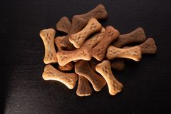 Bone shaped dog cookies or treats, on dark wood background stock photos