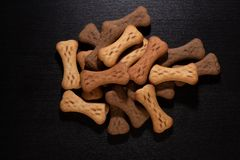 Bone shaped dog cookies or treats, on dark wood background royalty free stock photography