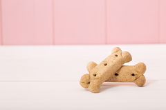 Bone shaped dog treats. On pink wooden wall stock photos