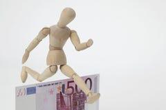 Boneca articulada que salta sobre um 500-Euro-Banknote imagens de stock
