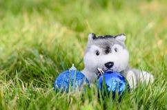 Boneca bonito do cachorrinho com a bola do Natal na grama verde Fotografia de Stock