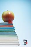 Boneca da estudante e uma maçã em livros Imagens de Stock