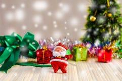 A boneca de Santa Claus contra uma árvore de Natal com a caixa de presente na madeira Foto de Stock