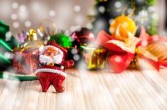 A boneca de Santa Claus contra uma árvore de Natal com a caixa de presente na madeira Foto de Stock Royalty Free