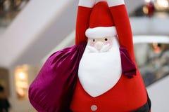 Boneca de Santa Claus Uma boneca macia do luxuoso de Santa Claus do gigante está pendurando para baixo do teto com um saco grande fotos de stock
