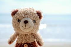 Boneca de sorriso do urso de peluche na praia imagem de stock royalty free