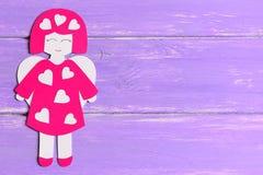 Boneca do anjo com os corações feitos do cartão Anjo bonito no fundo de madeira lilás com espaço da cópia para o texto Imagens de Stock Royalty Free