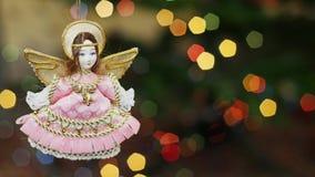 Boneca do anjo do Natal em luzes do bokeh Área do título filme