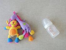 Boneca do brinquedo do bebê e garrafa de leite vazia Imagens de Stock