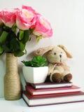 Boneca do coelho que senta-se no caderno com o artificial da vida da planta verde ainda Fotografia de Stock