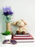 Boneca do coelho que senta-se no caderno com o artificial da vida da planta verde ainda Fotos de Stock