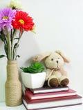 Boneca do coelho que senta-se no caderno com o artificial da vida da planta verde ainda Fotos de Stock Royalty Free