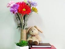 Boneca do coelho que senta-se no caderno com o artificial da vida da planta verde ainda Imagens de Stock