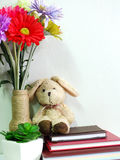 Boneca do coelho que senta-se no caderno com o artificial da vida da planta verde ainda Imagem de Stock