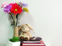 Boneca do coelho que senta-se no caderno com o artificial da vida da planta verde ainda Fotografia de Stock Royalty Free