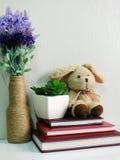 Boneca do coelho que senta-se no caderno com o artificial da vida da planta verde ainda Imagens de Stock Royalty Free