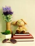 Boneca do coelho que senta-se no caderno com o artificial da vida da planta verde ainda Foto de Stock Royalty Free