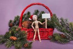 Boneca do manequim que guarda uma posição vazia do sinal na frente da cena invernal do Natal fotografia de stock royalty free