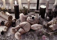Boneca do vudu com velas pretas e os rolos antigos Fotografia de Stock Royalty Free