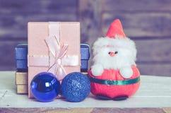 Boneca e caixas de presente de Santa com madeira Fotografia de Stock Royalty Free