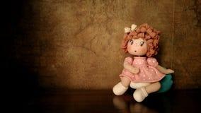 A boneca está sentando-se na frente da parede velha Imagem de Stock Royalty Free
