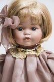 A boneca feito a mão da porcelana cerâmica com cabelo louro e o rosa vestem-se fotografia de stock royalty free