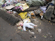 A boneca-menina com cabelo dourado encontra-se entre os restos na vestidura Imagens de Stock Royalty Free