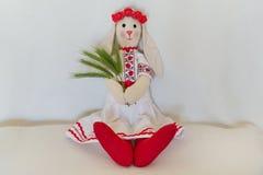 A boneca no traje popular ucraniano nacional, mantém os spikelets Bunny Rabbit feito a mão senta-se em um fundo claro fotos de stock royalty free