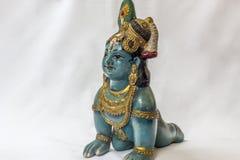 Boneca pequena muito velha do krishna do senhor com os ornamento tradicionais pintados na cor azul colocada em um contexto branco foto de stock royalty free