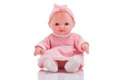 Boneca plástica pequena bonito com os olhos azuis que sentam o isolado Imagem de Stock Royalty Free