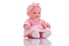 Boneca plástica pequena bonito com os olhos azuis que sentam o isolado imagem de stock