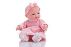 Boneca plástica pequena bonito com os olhos azuis que sentam o isolado imagens de stock