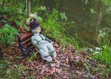 Boneca que senta-se no banco no parque do outono Envelhecido e esquecido fotos de stock