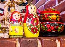 Bonecas aninhadas e utensílios de madeira pintados que incluem um tijolo e uma tabela de madeira Fotografia de Stock Royalty Free