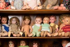 Bonecas antigas que sentam-se em um armário Fotografia de Stock