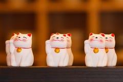 Bonecas cerâmicas do gato de Maneki Neko na prateleira de madeira Foto de Stock