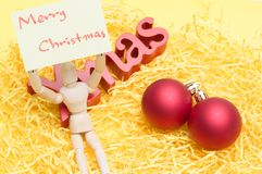 Bonecas comum que guardam notas amarelas com Feliz Natal: christma Imagem de Stock