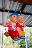 Bonecas cozidas da argila - avô tailandês e avó que jogam o balanço Imagem de Stock