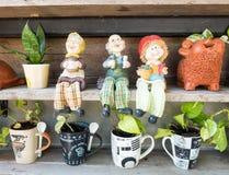 Bonecas da família e potenciômetro da árvore na prateleira Fotos de Stock