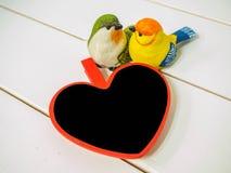 Bonecas do pássaro feitas do estuque no fundo branco da cadeira com coração pequeno da placa foto de stock royalty free