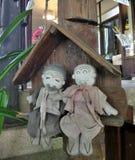 Bonecas idosas felizes de pano dos pares que sentam-se na casa de campo de madeira Fotografia de Stock