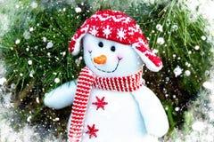 Boneco de neve alegre e engraçado em um chapéu e em um lenço vermelhos em um fundo da árvore de Natal imagens de stock royalty free
