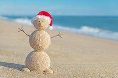 Boneco de neve arenoso do smiley no chapéu de Santa Conceito do feriado por anos novos Fotografia de Stock Royalty Free