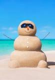 Boneco de neve arenoso engraçado nos óculos de sol na praia ensolarada tropical do oceano imagens de stock royalty free