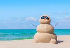 Boneco de neve arenoso positivo nos óculos de sol na praia tropical do oceano ensolarado foto de stock