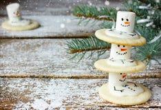 Boneco de neve bonito das cookies do Natal por feriados de inverno na madeira nevado Imagem de Stock