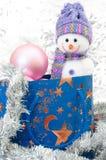 Boneco de neve com caixa de presente azul e a quinquilharia cor-de-rosa em um fundo do si Foto de Stock