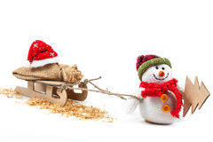 Boneco de neve com pequeno trenó, árvore de Natal e roupa de Santa Claus Fotografia de Stock Royalty Free